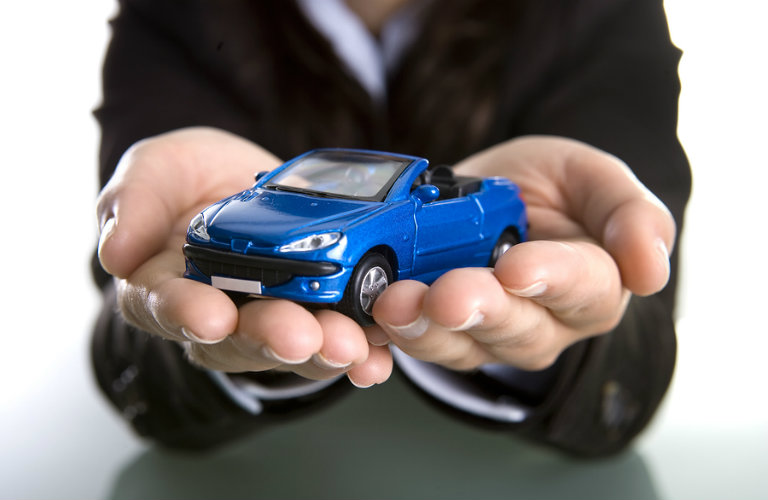 closeup of woman's hands holding blue toy car