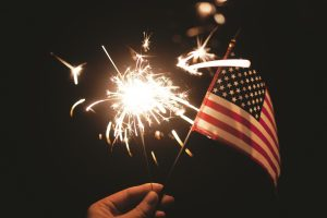 person holding a small American flag and a sparkler