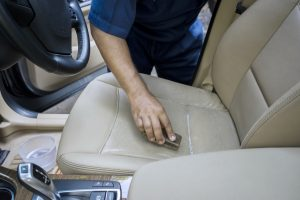 Close up of worker hand using a brush to clean the leather car seat and remove dust or dirt