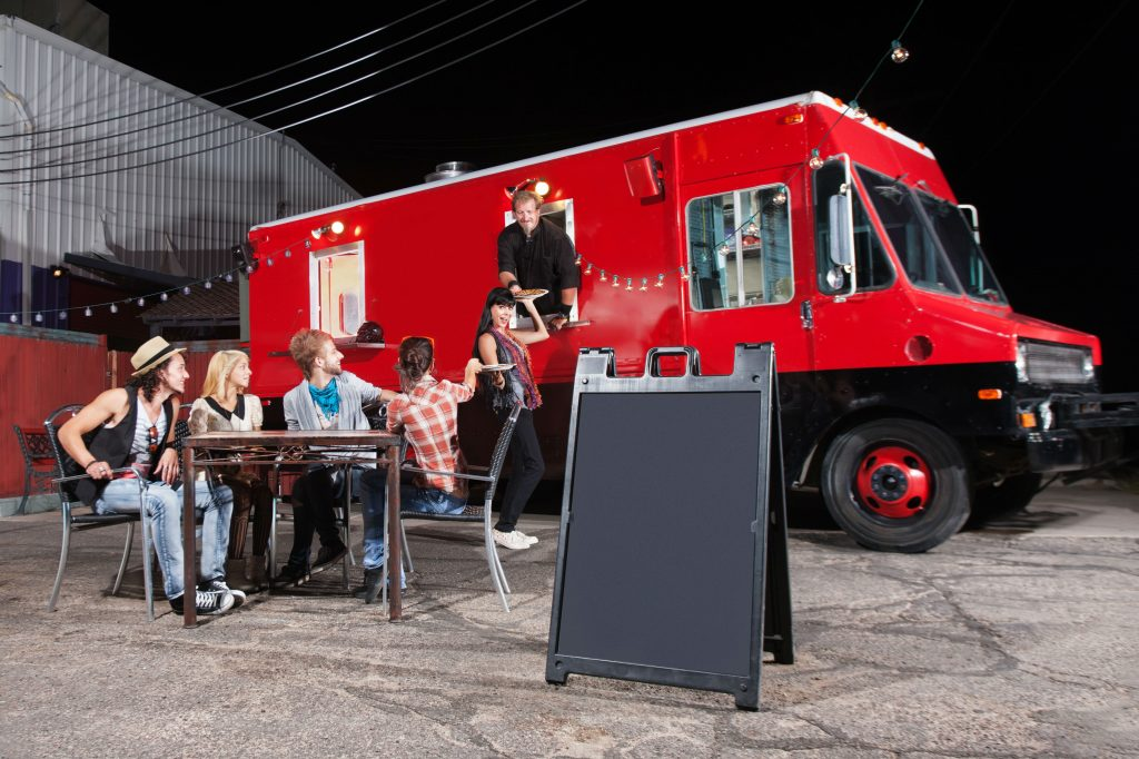 people enjoying food from a food truck