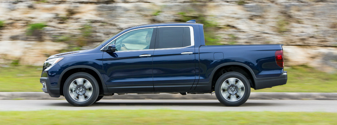 2019 Honda Ridgeline exterior side shot with obsidian blue pearl paint color driving alongside a rock cliffside