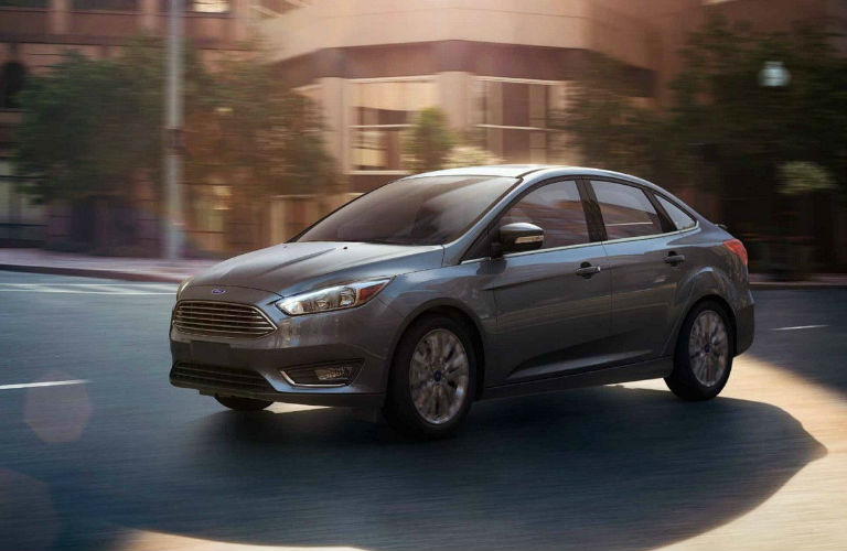 2018 Ford Focus sedan driving in front of building