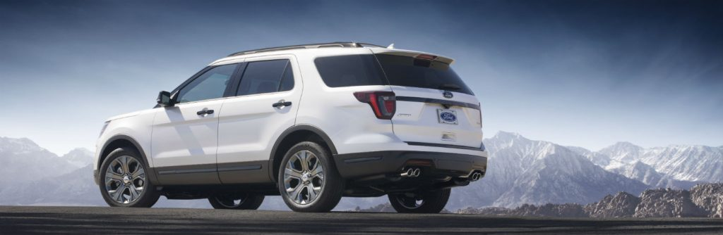 White Ford Explorer parked in front of mountainous background