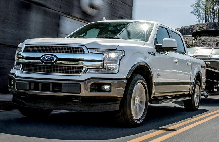 2018 Ford F-150 King Ranch towing a boat down a two-lane road