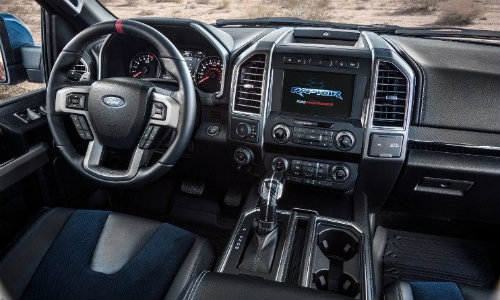 Steering wheel and center touchscreen of 2019 Ford Raptor with blue-accented seats prominent