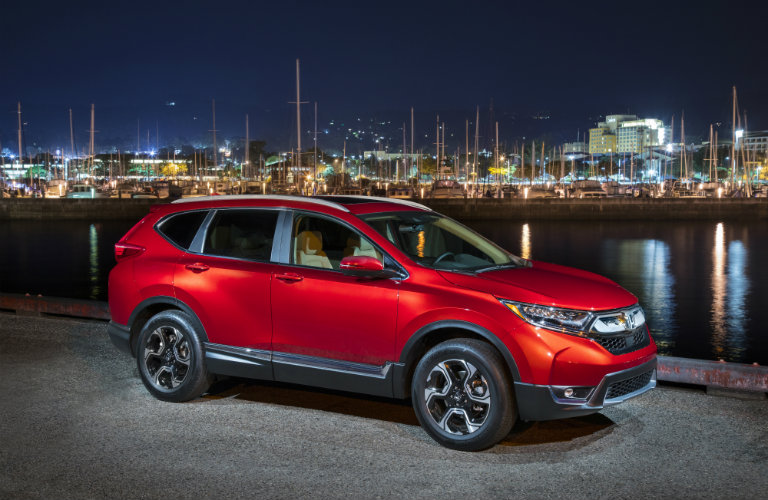Exterior view of a red 2018 Honda CR-V parked next to a body of water with a marina in the background