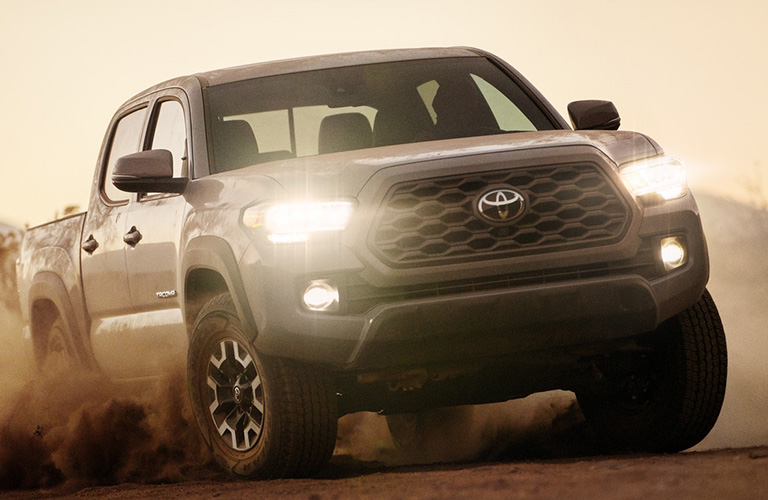 A head-on photo of the 2020 Toyota Tacoma driving through sand.