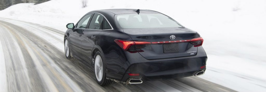 Driver's side rear angle view of dark blue 2020 Toyota Avalon driving on a snowy road
