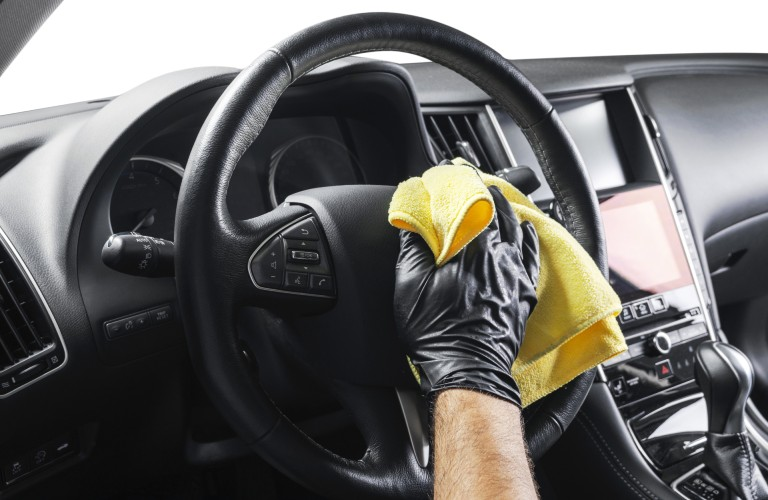 A steering wheel inside of a vehicle vehicle being cleaned by someone with a yellow rag.