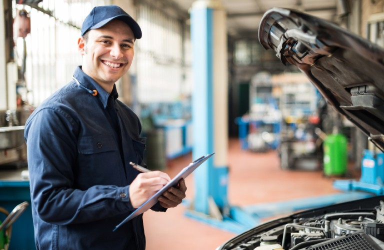 A service mechanic smiling while doing a checklist for a vehicle.